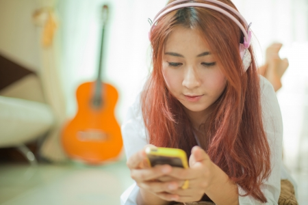 Young asian beautiful woman with smart phone and listening to music Imagens