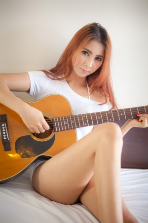 Sexy asian girl with a acoustic guitar in bedroom photo