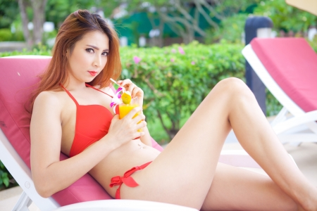 Beautiful young asian woman in red bikini lying on a deckchair at the beach photo