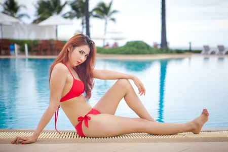 sexy asian girl: Sexy asian girl in red bikini lying near swimming pool