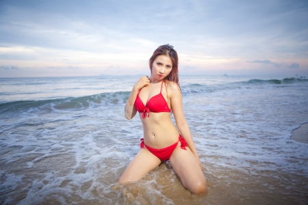 Belle femme asiatique en bikini rouge posant � la plage photo