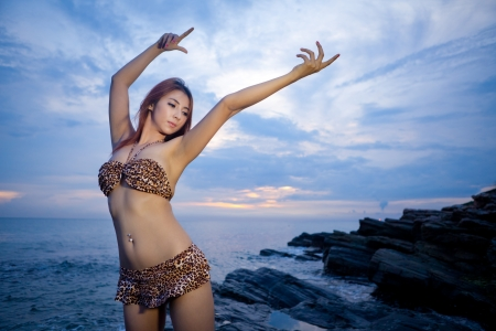 sexy asian woman: Sexy asian model posing at the stone on sunset Stock Photo