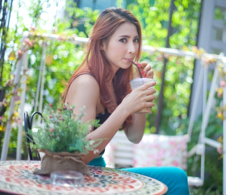 woman drinking tea: Young asian woman drinking ice coffee at restaurant