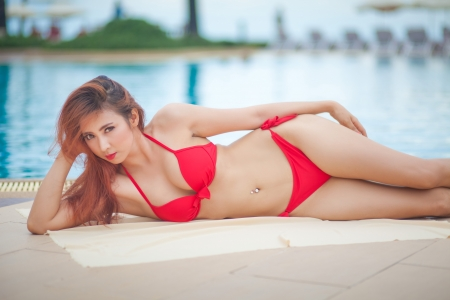 Sexy asian girl in red bikini lying near swimming pool photo