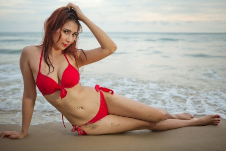 Beautiful asian woman in red bikini posing at beach photo