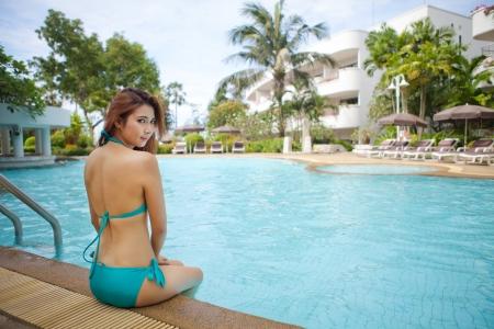 blue bikini: Sexy asian girl in blue bikini sitting near swimming pool