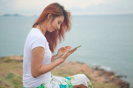 Young asian woman use tablet pc on mountain and sea photo