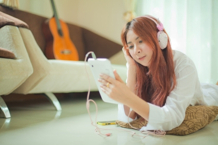 Young asian beautiful woman with smart phone and listening to music at home photo