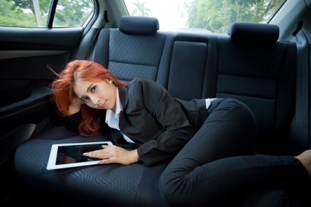 Young business asian woman inside her car using a tablet photo