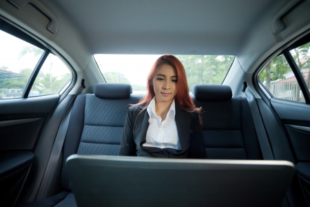 Beautiful young business asian woman using laptop in a car photo