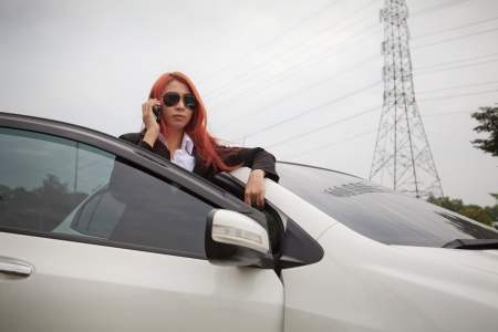 Beautiful young business asian woman using a smart phone and car photo