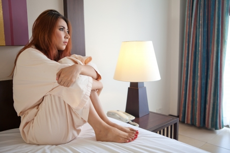 Asian sad woman sitting on the bed in bedroom photo