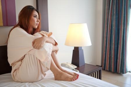 chateado: Mulher triste asi�tico sentado na cama no quarto