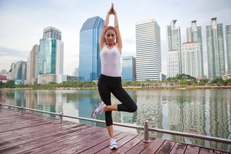 Beautiful young asian woman doing stretching exercise in the city photo