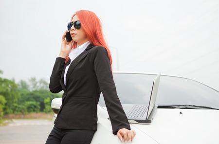 Beautiful young business asian woman using laptop and mobile phone and car photo