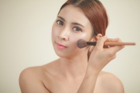 Beautiful young asian woman applying blusher photo