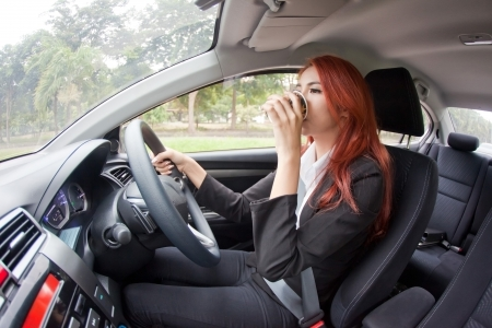 Business asian woman drinking coffee while driving