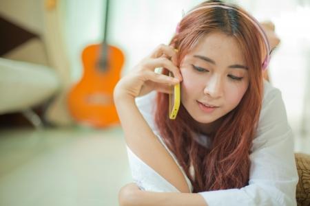 smart: Jonge Aziatische mooie vrouw met slimme telefoon en het luisteren naar muziek