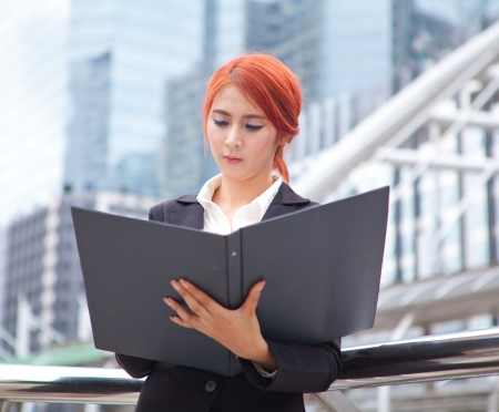 Young business asian woman with document at modern city photo