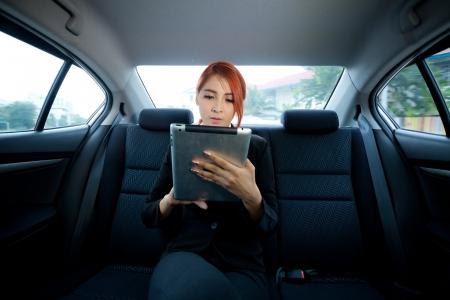 タブレットを使用して彼女の車の中の若いビジネス アジア女性