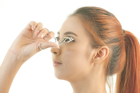 wider: Young asian beautiful girl making her eyelashes wider with curler Stock Photo