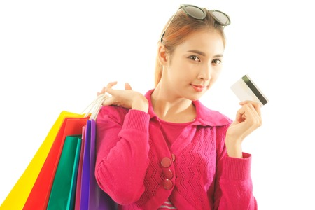 Portrait of young asian woman holding credit card and shopping bags isolated on white background photo