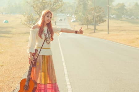 hitchhiking: Hippie girl with guitar hitchhiking on countryside road Stock Photo