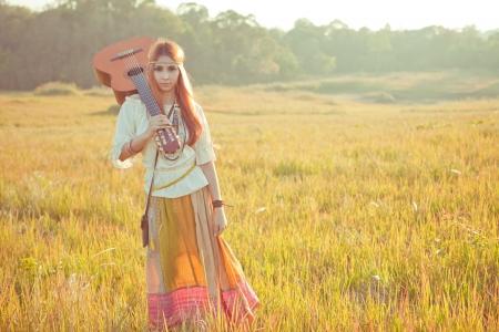 mujer hippie: Mujer del Hippie que recorre en campo de oro con la guitarra ac�stica