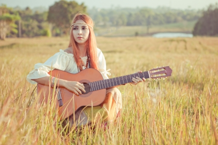 girl playing guitar: Pretty country hippie girl playing guitar on grass
