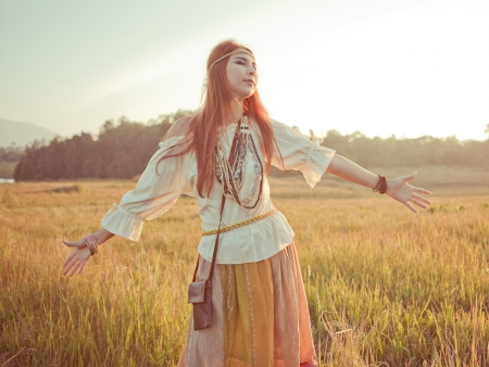 mujer hippie: La mujer del Hippie con los brazos extendidos en el campo de oro en la puesta del sol