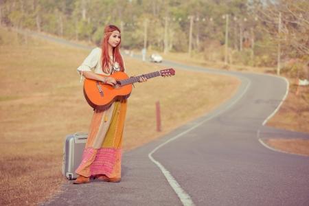 mujer hippie: Mujer Hippie tocando m�sica y bailando en el camino rural