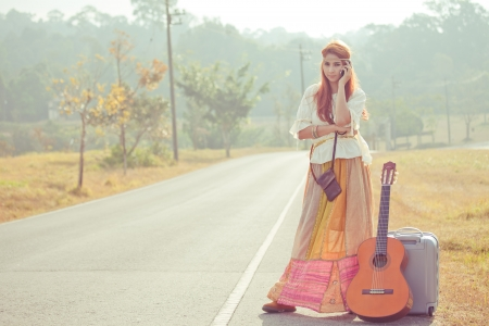 Beautiful young hippie girl using mobile phone on the country road photo