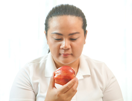 selects: Fat asian woman with apple on white