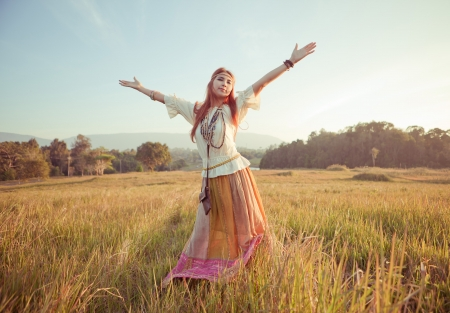 Hippie woman with arms outstretched in golden field on sunset photo