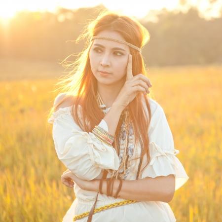 Hippie woman posing in golden field on sunset photo