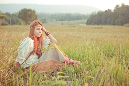 Country hippie girl sitting at golden field