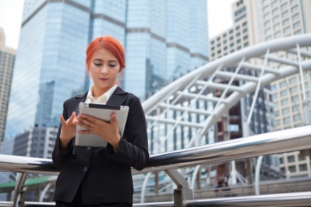 Young business asian woman with tablet at modern city photo