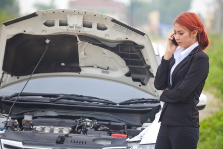 Young beautiful business asian woman with car broke down