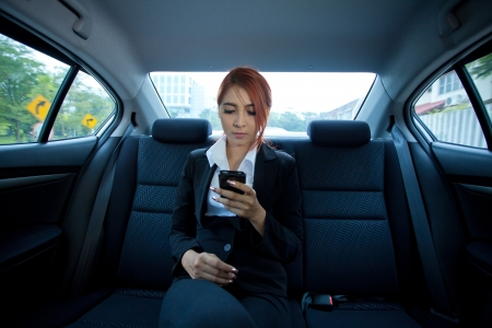 Beautiful young business asian woman using a smart phone in a car photo