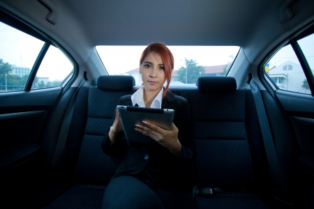 Young business asian woman inside her car using a tablet