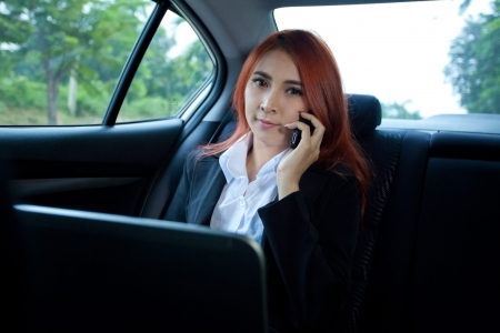 Beautiful young business asian woman using laptop and mobile phone in a car photo