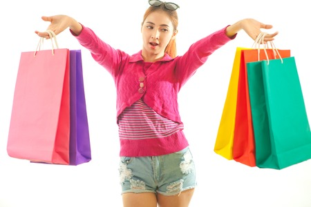 Portrait of young asian woman holding shopping bags isolated on white background photo