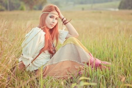 Country hippie girl sitting at golden field photo