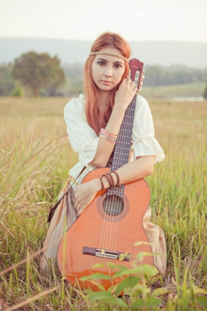 Pretty country hippie girl playing guitar on grass photo