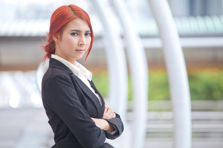 Portrait of young business asian woman standing and smiling arms crossed in modern city photo