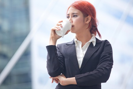 Portrait of young business asian woman standing with coffee in modern city photo