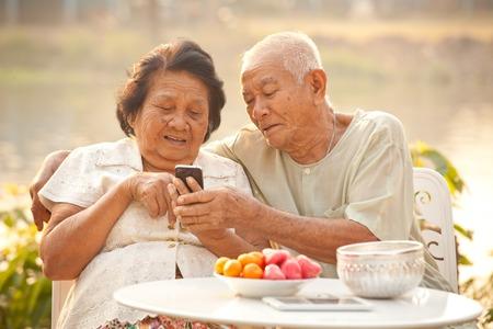 屋外の背景に携帯電話を使用して幸せなアジア シニア カップル