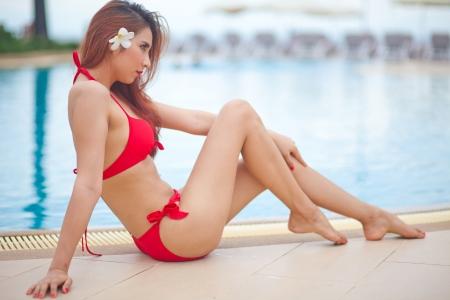 sexy bikini girl: Sexy asian girl in red bikini lying near swimming pool