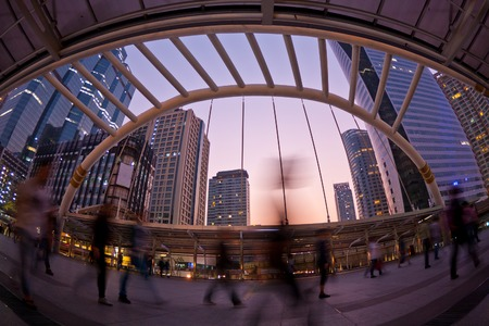 都市の景観の日没を明るい背景から歩く人 写真素材
