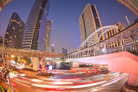 time lapse: Night traffic light trails and skytrain in Bangkok city, Thailand